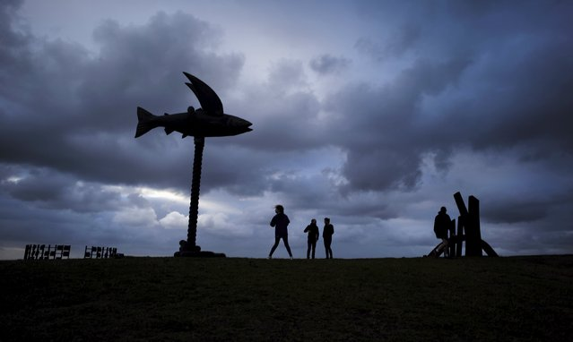 A giant fiberglass and steel sculpture entitled 'Flying Fish' by Australian artists Gillie and Marc Schattner dwarfs visitors to the 19th annual Sculptures by the Sea exhibition in Sydney, October 23, 2015. (Photo by Jason Reed/Reuters)