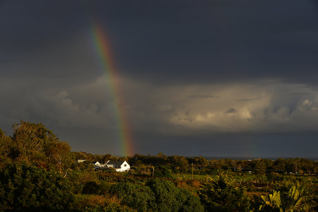 A rainbow forms over the Atlantic ocean as storm clouds approach a small farm on the south peninsula of Cape Town, South Africa, August 5, 2014. A series of cold fronts have brought wet, windy and cold weather to the Cape as the 2014 winter months are recording unusually high precipitation levels. (Photo by Nic Bothma/EPA)