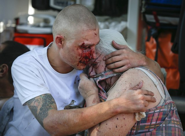 A man comforts a woman, after both were wounded by what locals say was recent shelling by Ukrainian forces in Donetsk, in this August 23, 2014 file photo. (Photo by Maxim Shemetov/Reuters)