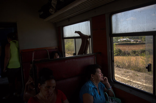 In this March 23, 2015 photo, a commuter puts his feet up in a train traveling from Santiago de Cuba to Santa Clara, in the province of Holguin, Cuba. The trip from Havana to Santiago, 475 miles (765 kilometers) to the east, takes an average of 15 hours, if the train doesn't break down. A slightly more reliable train with air conditioning currently is not running while it undergoes repairs. (Photo by Ramon Espinosa/AP Photo)