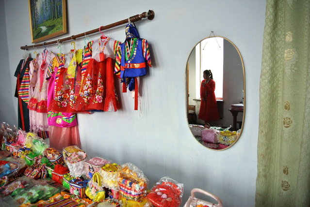 A North Korean seller is reflected in a mirror as she waits for customers at a shop in the northeastern North Korean border town of Sinuiju on December 15, 2012. (Photo by Wang Zhao/AFP Photo)