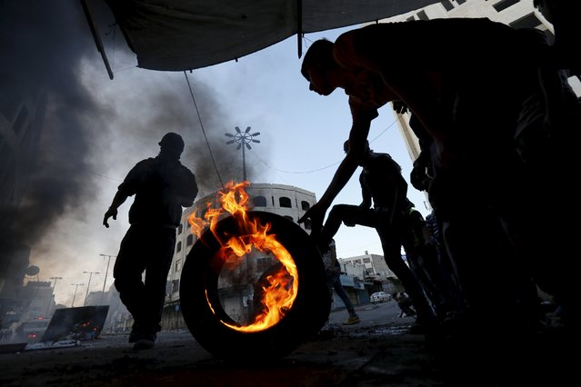 A Palestinian protester pushes a burning tyre during clashes with Israeli troops in the West Bank city of Hebron October 31, 2015. (Photo by Ammar Awad/Reuters)