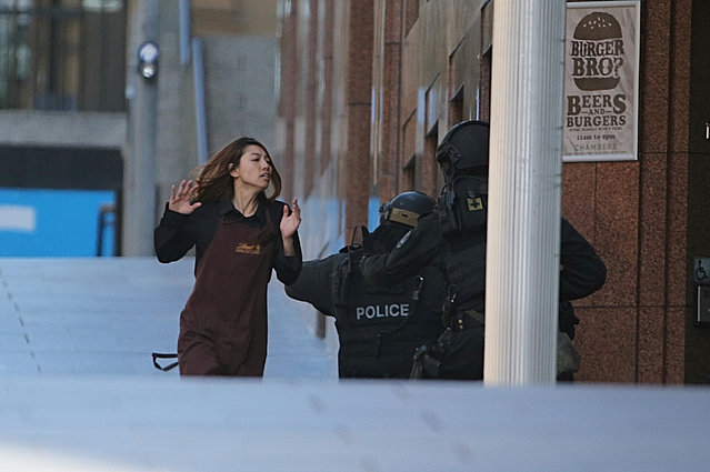 An armed tactical response police officer grabs a hostage as she flees from a cafe under siege at Martin Place in the central business district of Sydney, Australia, Monday, December 15, 2014. New South Wales state police would not say what was happening inside the cafe or whether hostages were being held. But television footage shot through the cafe's windows showed several people with their arms in the air. (Photo by Rob Griffith/AP Photo)