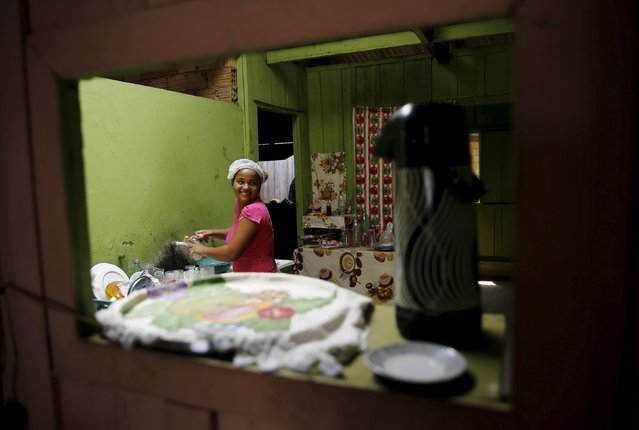 A woman washes dishes at a restaurant in Rio Pardo next to Bom Futuro National Forest, in the district of Porto Velho, Rondonia State, Brazil, August 31, 2015. A popular dish is a stew made of beef and bean. (Photo by Nacho Doce/Reuters)