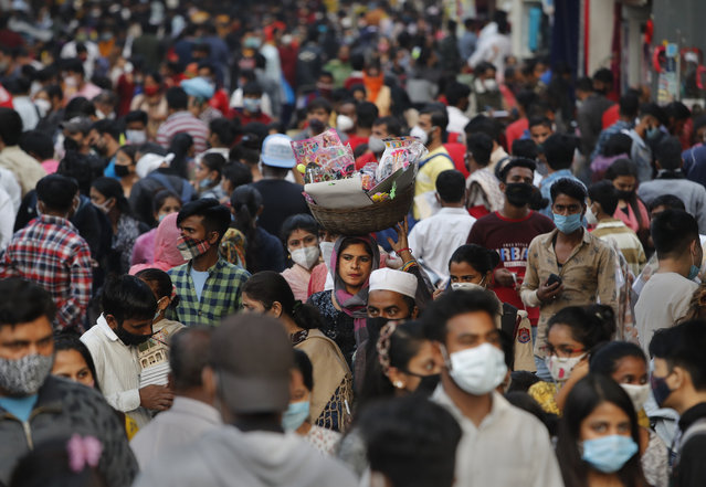 A woman without a mask walks in a crowded market selling toys in New Delhi, India, Thursday, November 12, 2020. Authorities in New Delhi have banned firecrackers and are appealing to people to celebrate the Hindu festival of lights at home. Coronavirus infections have been rising in the capital and authorities are worried large festival crowds will worsen the virus situation. (Photo by Manish Swarup/AP Photo)