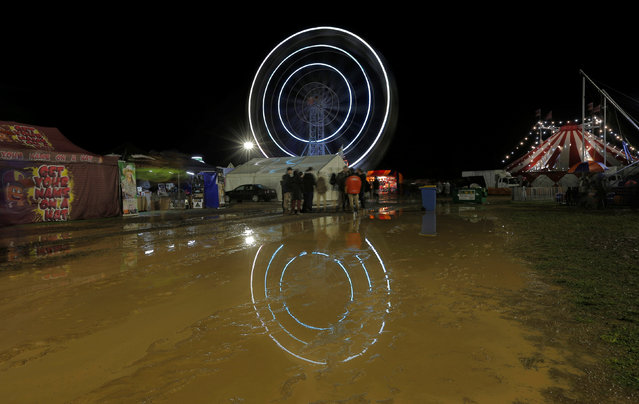A spinning ferris wheel is reflected in mud after heavy rains flooded the sideshow carnival at the Deni Ute Muster in Deniliquin, New South Wales, Australia, September 30, 2016. (Photo by Jason Reed/Reuters)