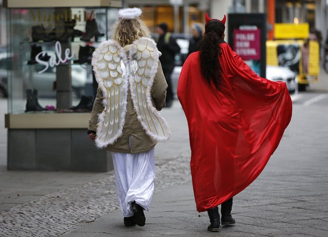 Two women, one dressed as an angel (L) and one as a devil, walk during a Christmas shopping promotion event at the main shopping street Kurfuerstendamm boulevard in Berlin December 13, 2014. (Photo by Fabrizio Bensch/Reuters)