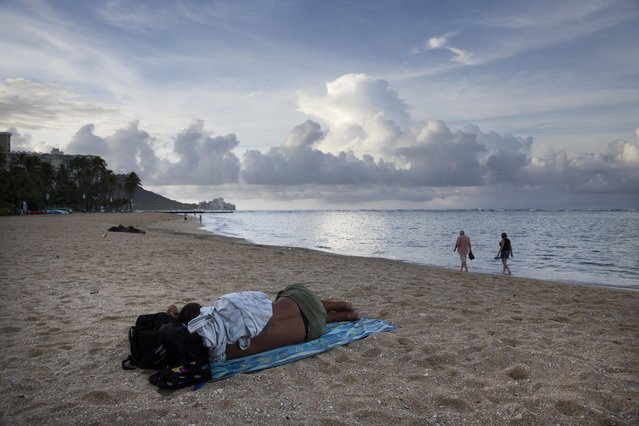 In this Tuesday, August 25, 2015 photo, a homeless man sleeps on Fort DeRussy in Waikiki as two tourists take a morning stroll along the beach in Honolulu. In 2014, after visitors complained about too many homeless people living near Waikiki Beach, the city banned sitting and lying down on sidewalks. (Photo by Jae C. Hong/AP Photo)