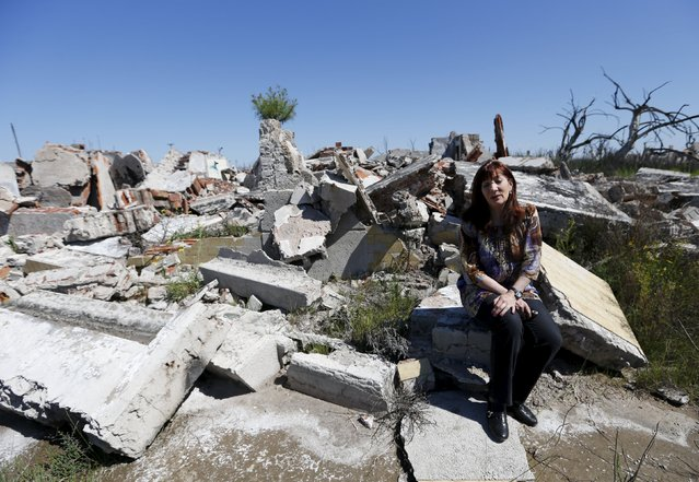 Mirta Estoessel, sits on her former home in the onetime spa and resort town Epecuen, November 6, 2015. (Photo by Enrique Marcarian/Reuters)