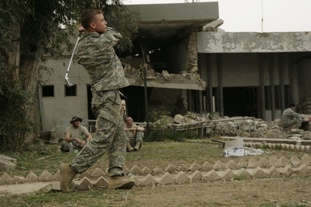 In this March 25, 2008 file photo, U.S. Army Staff Sgt. Chad Caldwell, 24, from Spokane, Wash., plays golf as his comrades from K Troop, Third Squadron, Third Armored Cavalry Regiment, look on at Combat Outpost Rabiy in Mosul, Iraq. (Photo by Maya Alleruzzo/AP Photo)