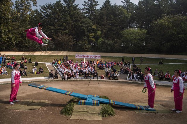 In a photo taken on October 15, 2016 competitors take part in a see-saw event during the 13th People's Games at Moran Hill park in Pyongyang. (Photo by Kim Won-Jin/AFP Photo)