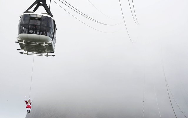A man disguised as Santa Claus, suspended from the Sugar Loaf's Cable car, waves at visitors upon arrival to the Sugar Loaf mountain, in Rio de Janeiro, Brazil, on December 05, 2020. (Photo by Mauro Pimentel/AFP Photo)