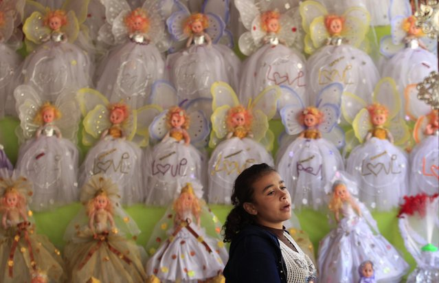 "A girl is seen where traditional doll toys are displayed for sale to celebrate the birthday of prophet Muhammad, also known as ""mawlid al nabi"", which will fall next week, in a makeshift tent in Cairo, December 30, 2014. (Photo by Mohamed Abd El Ghany/Reuters)"