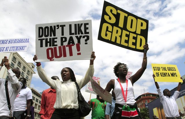 Protestors carry placards as they participate in a demonstration against lawmakers' salary demands near parliament buildings in the capital Nairobi, May 14, 2013. (Photo by Thomas Mukoya/Reuters)