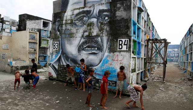 Children play in front of a mural at Navotas Public Cemetery, Metro Manila in the Philippines, October 23, 2016. (Photo by Erik De Castro/Reuters)