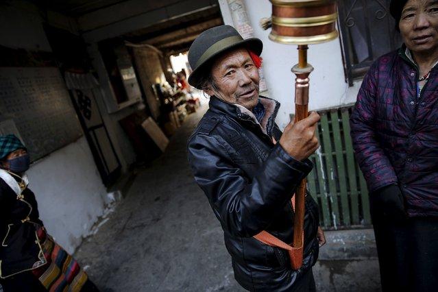 A Tibetan man spins a prayer wheel in the old part of Lhasa, Tibet Autonomous Region, China November 16, 2015. (Photo by Damir Sagolj/Reuters)