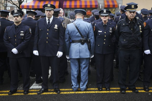 Law enforcement officers stand, with some turning their backs, as New York City Mayor Bill de Blasio speaks on a monitor outside the funeral for NYPD officer Wenjian Liu in the Brooklyn borough of New York January 4, 2015. Tens of thousands of law enforcement officers from across the country gathered on Sunday for the funeral of the second of two New York City policemen killed last month in an ambush that galvanized critics of Mayor de Blasio. (Photo by Shannon Stapleton/Reuters)