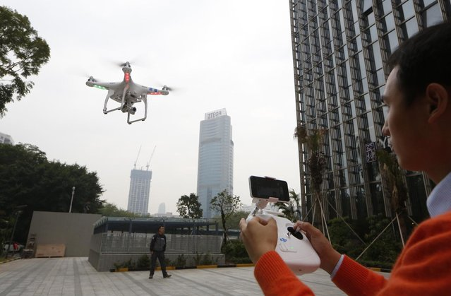 In this Monday, December 15, 2014 photo, a staff member from DJI Technology Co. demonstrates the remote flying with his Phantom 2 Vision+ drone in Shenzhen, south China's Guangdong province. (Photo by Kin Cheung/AP Photo)