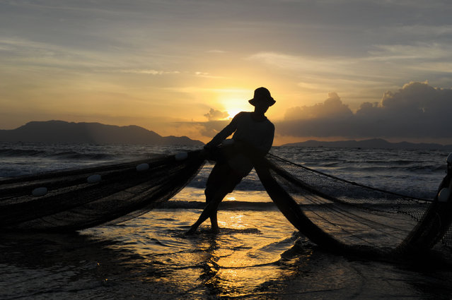 In this picture taken on September 26, 2016 show a fisherman cleaning a net in Banda Aceh, Aceh province, after overnight fishing. Indonesia's economy accelerated in the second quarter as government stimulus plans came to fruition, a report said last week. (Photo by Chaideer Mahyuddin/AFP Photo)