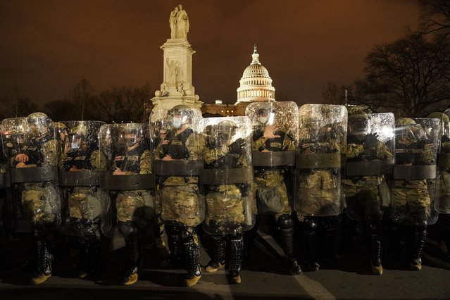 District of Columbia National Guard stand outside the Capitol, Wednesday night, January 6, 2021, after a day of rioting protesters. It's been a stunning day as a number of lawmakers and then the mob of protesters tried to overturn America's presidential election, undercut the nation's democracy and keep Democrat Joe Biden from replacing Trump in the White House. (Photo by John Minchillo/AP Photo)