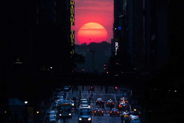 "The sun sets along 42nd Street in Manhattan during an annual phenomenon known as ""Manhattanhenge"", when the sun aligns perfectly with the city's transit grod, Wednesday, May 29, 2013, in New York. (Photo by John Minchillo/AP Photo)"