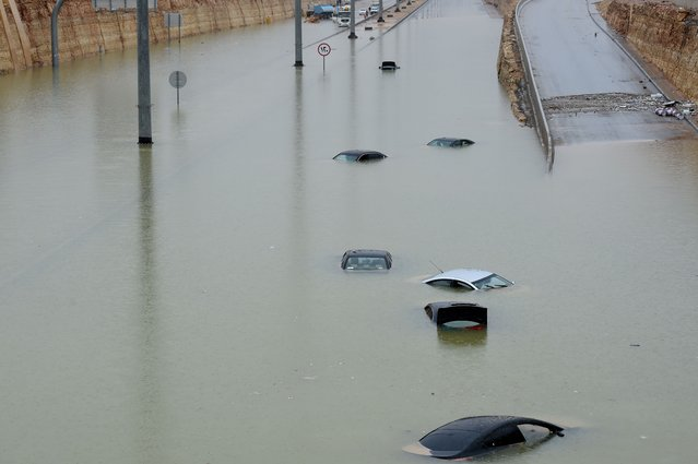 Vehicles are seen submerged in water in a flooded highway in western Riyadh following heavy rainfall across most of the country on November 25, 2015. Schools were closed for a second day in Saudi Arabia as rain continued to fall. (Photo by Fayez Nureldine/AFP Photo)