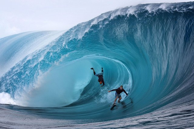 US Garrett McNamara (L) and US Mark Healey (R) compete during a free session of surf tow in, in the southern Pacific ocean island of Tahiti, French Polynesia, on June 1, 2013 in Teahupoo. (Photo by Gregory Boissy/AFP Photo)
