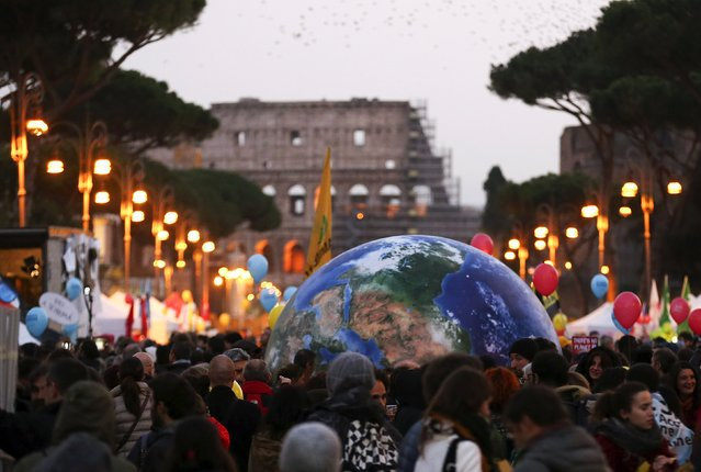 Protesters carry a globe-shaped balloon in front of Rome's Colosseum during a rally held the day before the start of the 2015 Paris Climate Change Conference (COP21), in Rome, Italy, November 29 2015. (Photo by Alessandro Bianchi/Reuters)