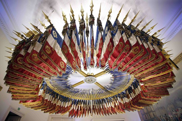 The tri-colour, blue, white and red flags and banners from 182 disbanded French military regiments are arranged in a circle as they hang from the ceiling in the Emblems Room (salle des Emblemes) at the Chateau de Vincennes, near Paris, France, December 2, 2015. (Photo by Charles Platiau/Reuters)