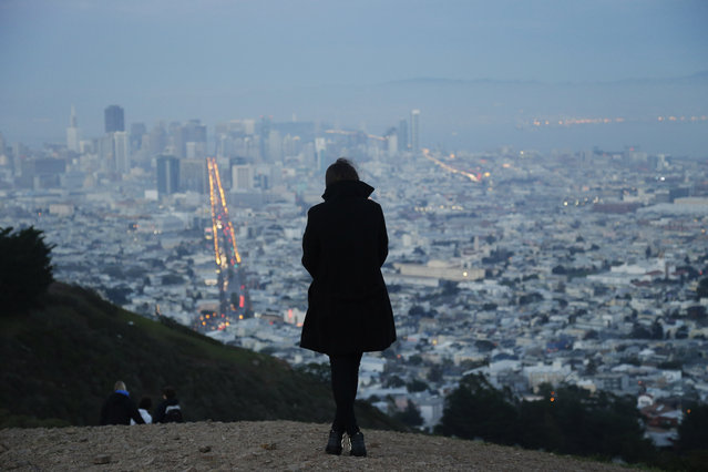 A visitor takes in a view of the downtown district from Twin Peaks on Friday, January 9, 2015, in San Francisco. (Photo by Marcio Jose Sanchez/AP Photo)