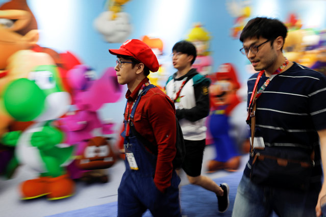 Attendees walk the floor at E3, the world's largest video game industry convention in Los Angeles, California on June 12, 2018. (Photo by Mike Blake/Reuters)