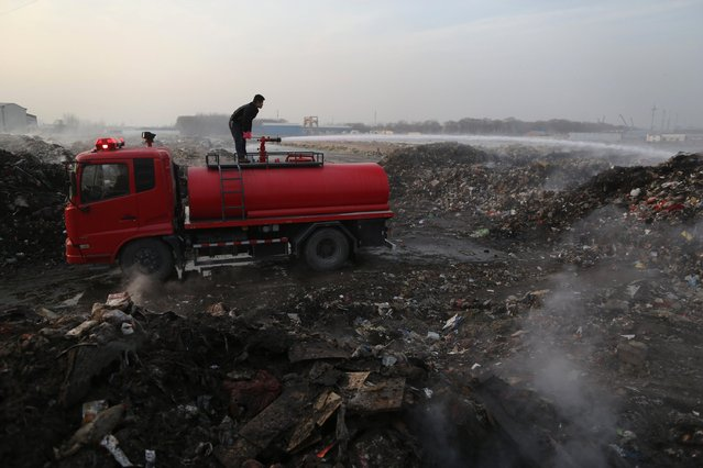 A worker sprays water as smokes rises at a waste transfer station in Beijing January 17, 2015. Biogas is produced inside the dump site when there are insufficient vehicles and manpower to transport the garbage away in time, according to an employee working at the station as quoted in local media. (Photo by Reuters/Stringer)