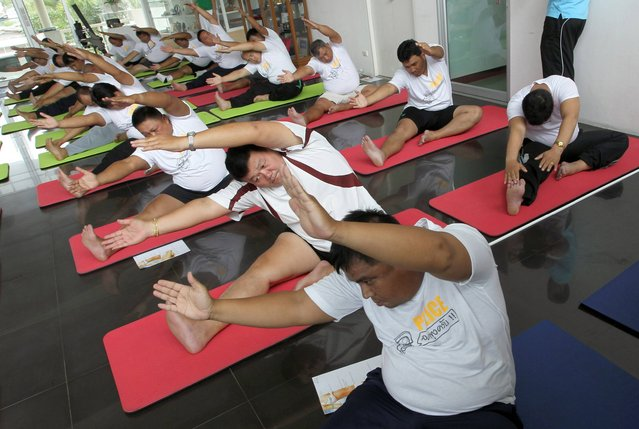In this photo taken Thursday, July 4, 2013, Thai police officers take part in a yoga program at a police training center in Bangkok, Thailand. As part of a national effort to reduce the numbers of overweight officers, Thailand has opened a 12-day boot camp to get police into shape. This week, 60 overweight officers from around the country were sent to suburban Bangkok for dawn-to-dusk exercise and lecture programs on living more healthy. (Photo by Apichart Weerawong/AP Photo)