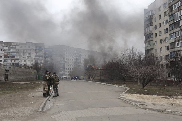 Ukrainian servicemen stand guard on a street near the burning building after a shelling by pro-Russian rebels of a residential sector in Mariupol, eastern Ukraine, January 24, 2015. Ten people were killed in shelling by pro-Russian separatists in the east Ukrainian port city of Mariupol on Saturday, the head of the Kiev-controlled Donetsk regional police said. (Photo by Nikolai Ryabchenko/Reuters)