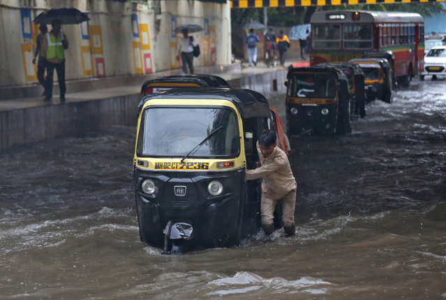 A man pushes his auto-rickshaw through a water-logged underpass after heavy rains in Mumbai, July 10, 2018. (Photo by Francis Mascarenhas/Reuters)