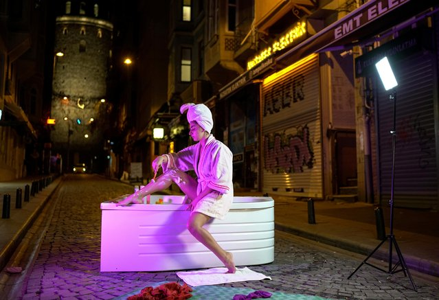 Artist Sayna Soleimanpour shaves her legs in a bathtub as she performs a photoshoot in protest against the mistreatment and alienation of Turkish women based on their clothing, during a two-day curfew amid the spread of the coronavirus disease (COVID-19), on a street leading to the historical Galata Tower in Istanbul, Turkey, late December 25, 2020. (Photo by Umit Bektas/Reuters)