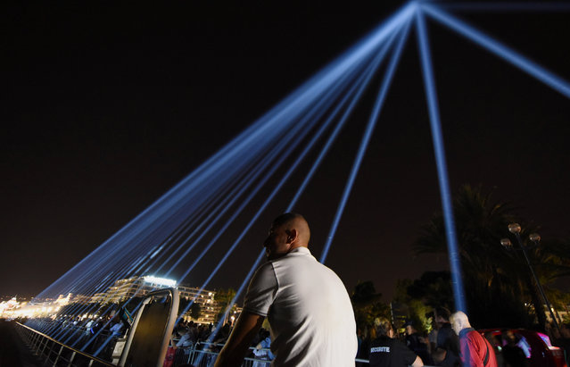 Eighty-six lights are projected into the sky to pay tribute to the victims of the truck attack along the Promenade des Anglais that killed 86 people two years ago on Bastille Day, in Nice, France, July 14, 2018. (Photo by Jean-Pierre Amet/Reuters)