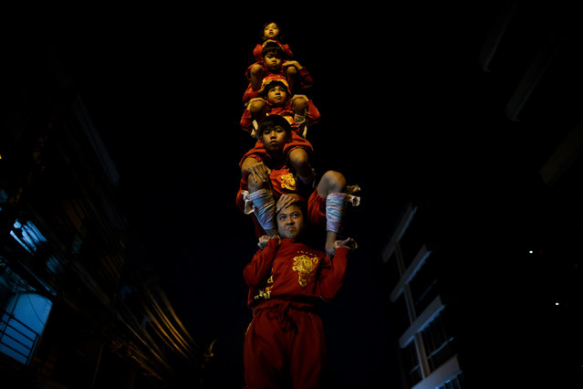 Young dancers of Look Chao Por Phra Kan Lion Dance troupe practice human pyramid acrobatic formation as motorists passing by during a dail​y training at an alleyway in Bangkok, Thailand, 23 January 2021. (Photo by Rungroj Yongrit/EPA/EFE)