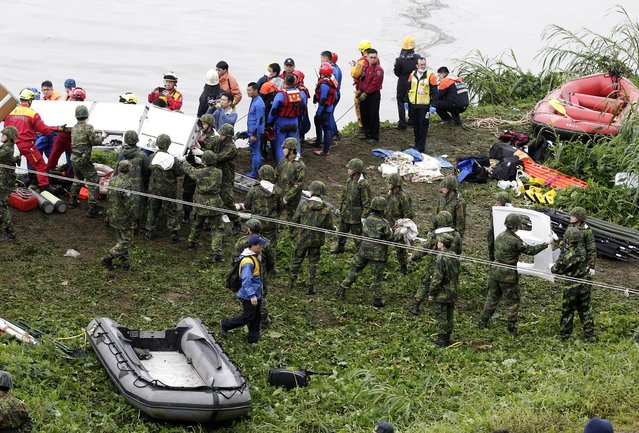 Rescuers and soldiers remove air plane parts after a TransAsia plane crashed into a river in New Taipei City, February 4, 2015. (Photo by Pichi Chuang/Reuters)