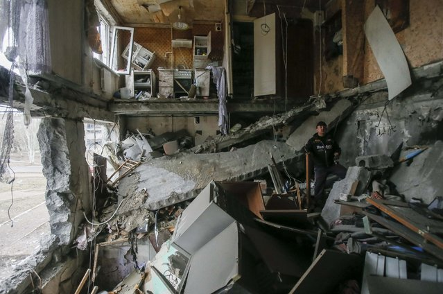 A man stands in a flat at a residential block damaged by a recent shelling in Yenakieve town, northeast from Donetsk, February 2, 2015. (Photo by Maxim Shemetov/Reuters)