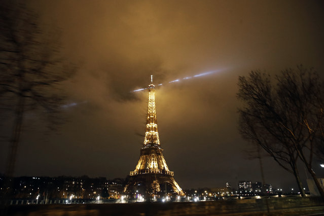 The Eiffel Tower is pictured during the curfew in Paris, Saturday, January 16, 2021. All of France is under a stricter curfew starting Saturday at 6 p.m. for at least 15 days to fight the spread of the coronavirus. (Photo by Christophe Ena/AP Photo)