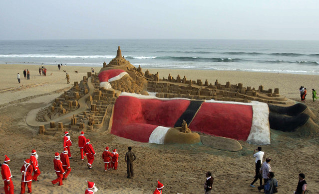 A general view of a sand sculpture of Santa Claus made by Indian sand artist Sudarshan Pattnaik and his students (dressed in Santa Claus) on the eve of Christmas is photographed at the golden beach at Puri, 65 km from Bhubaneswar, India, 24 December 2011. Despite Christians constitute only 2.3 per cent of India's population, Christmas is celebrated with much fanfare and zeal throughout the country. (Photo by EPA/Stringer)