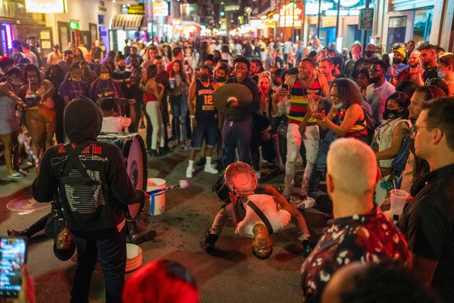 Steven Randall does a back bend while performing with his youth group Beats of Chapo on Bourbon Street which is bustling as the coronavirus disease (COVID-19) restrictions are eased in New Orleans, Louisiana, U.S., March 13, 2021. (Photo by Kathleen Flynn/Reuters)