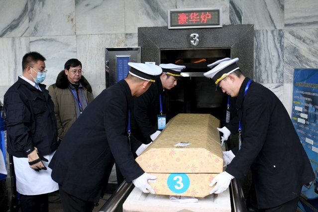 Cremation technicians put a coffin into a cremator as they participate in a skills competition in Beijing, China, December 27, 2015. According to local media, 54 cremation technicians from all over China took part in the competition. Judges scored them on how accurately they performed according to the national standard of cremation procedure. (Photo by Reuters/China Daily)