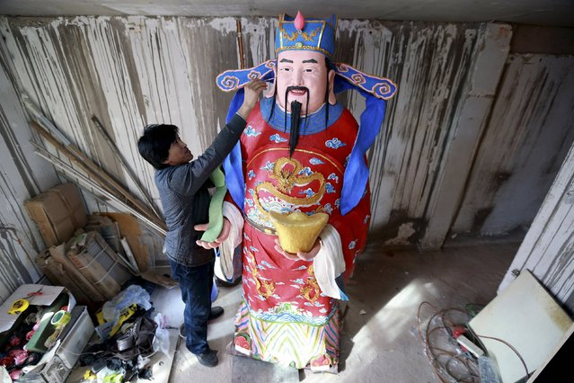 Yu Qiquan, a local dough modelling artist, polishes a giant sculpture of Cai Shen, or the God of Wealth, which will be put on display at a department store during the Chinese Lunar New Year, in Shenyang, Liaoning province February 9, 2015. The 2.28-metre-tall sculpture, was made from 150 kg (321 lbs.) of glutinous rice flour on steel frame. It took Yu two months to build and cost over 10,000 yuan ( $1,601). (Photo by Sheng Li/Reuters)