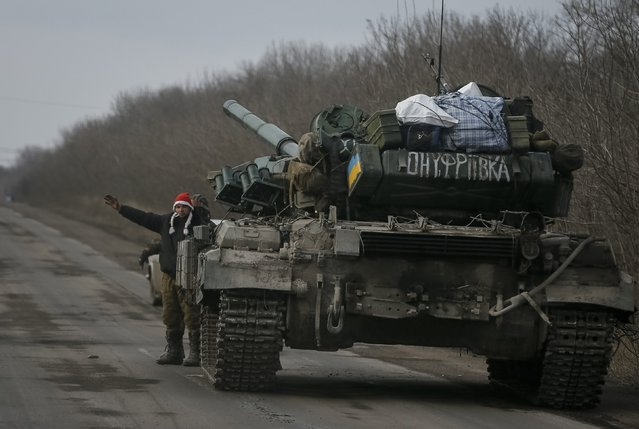 A Ukrainian serviceman wearing a new year's hat waves at his comrades while standing beside his tank near Debaltseve, eastern Ukraine, February 8, 2015. (Photo by Gleb Garanich/Reuters)