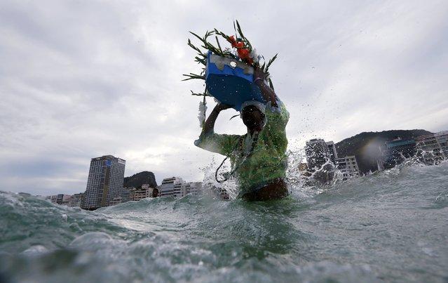 A follower of the Afro-Brazilian religion Umbanda carries offerings for Iemanja, goddess of the sea, in Copacabana Beach in Rio de Janeiro, December 29, 2015. (Photo by Ricardo Moraes/Reuters)