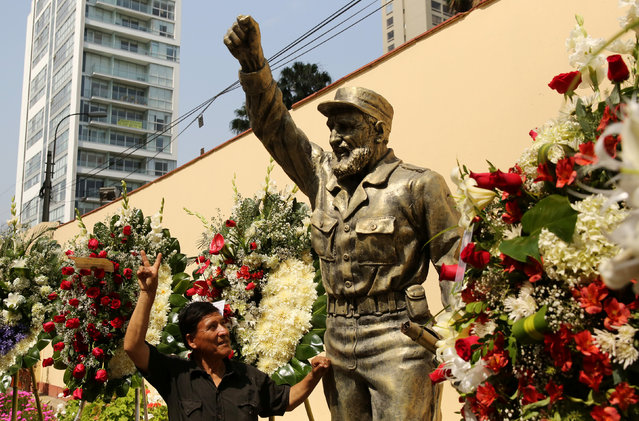 A man poses for a picture next to a statue of the late Cuban revolutionary leader Fidel Castro with flowers as part of the tribute following the announcement of his death inside the Cuban embassy in Lima, Peru, November 26, 2016. (Photo by Mariana Bazo/Reuters)