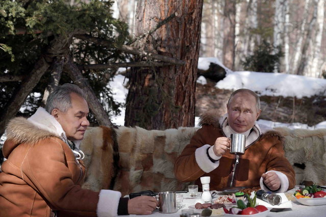 Russian President Vladimir Putin and Defence Minister Sergei Shoigu sit at a table during a holiday in the Siberian taiga, Russia on March 21, 2021. (Photo by Alexei Druzhinin/Sputnik/Kremlin via Reuters)
