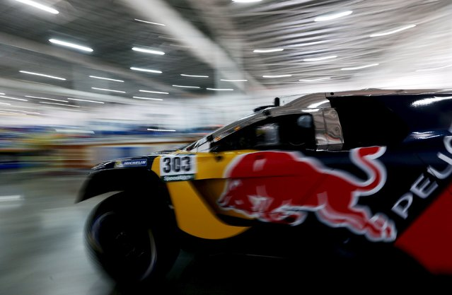 Peugeot driver Carlos Sainz of Spain drives his car inside the technical verification area ahead of the Dakar Rally 2016 in Buenos Aires, Argentina, January 1, 2016. (Photo by Marcos Brindicci/Reuters)